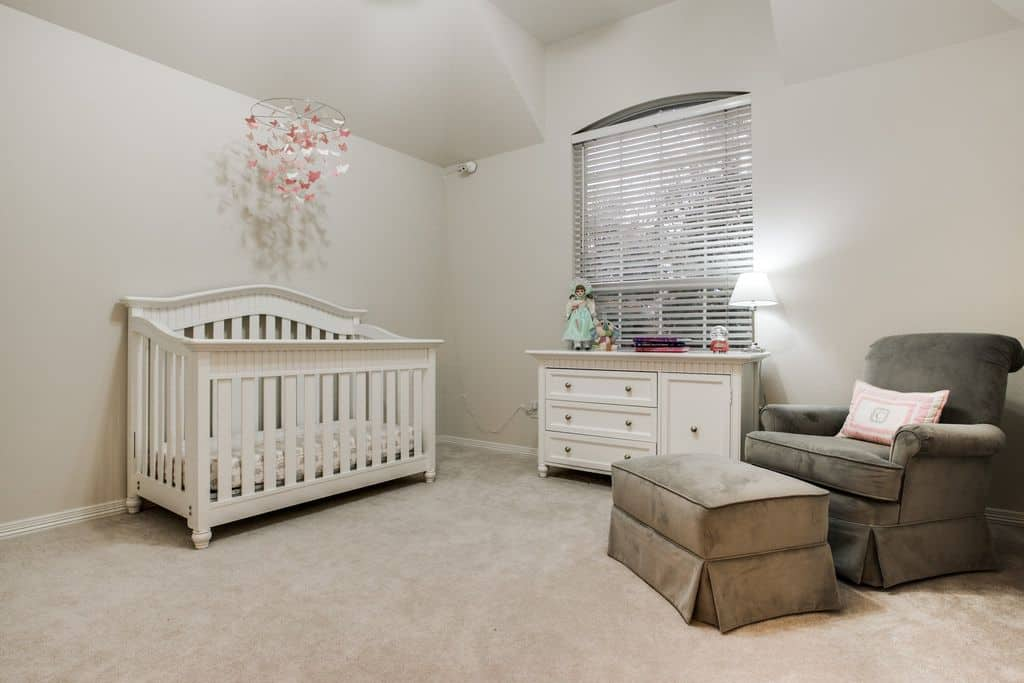 A gray skirted ottoman matches the velvet armchair in this minimalist nursery offering a white cabinet and crib paired with a pink butterfly mobile.