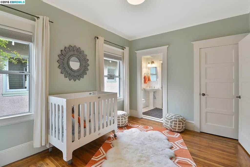 Light and airy nursery designed with layered rugs and a gorgeous floral mirror mounted above the white crib. It has hardwood flooring and picture windows covered in white curtains.