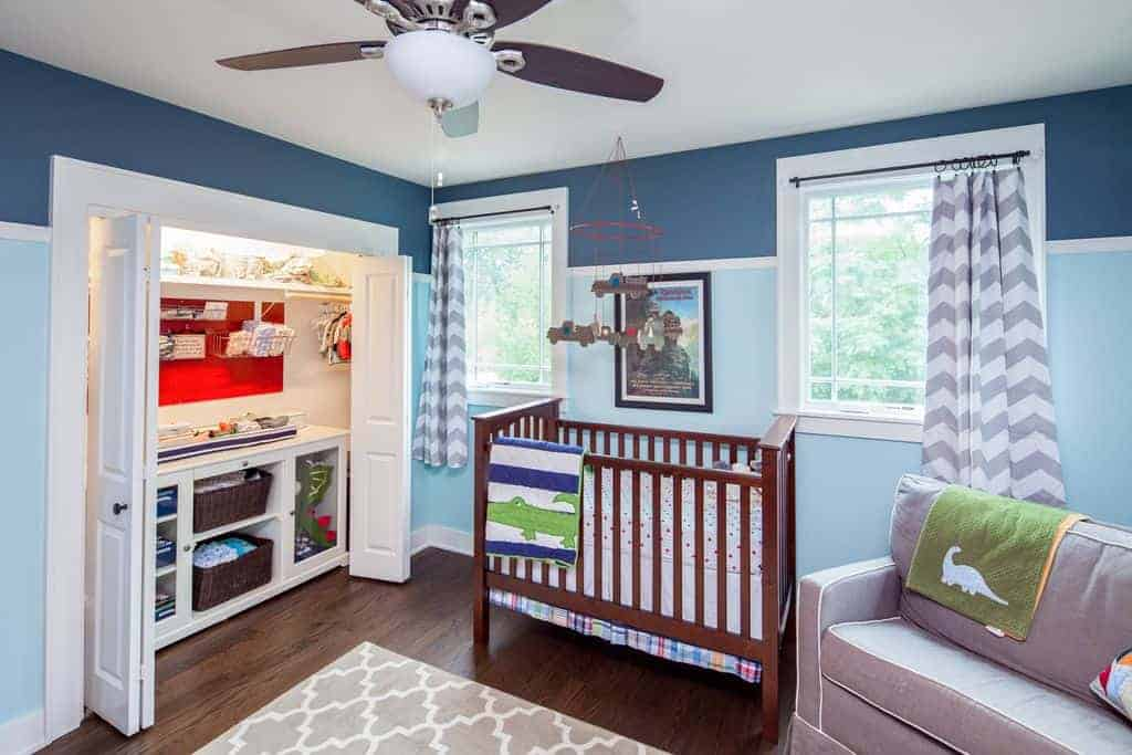 Cool nursery with a wooden crib and gray seat that complements the patterned area rug and chevron draperies. It includes a built-in closet enclosed in folding doors.