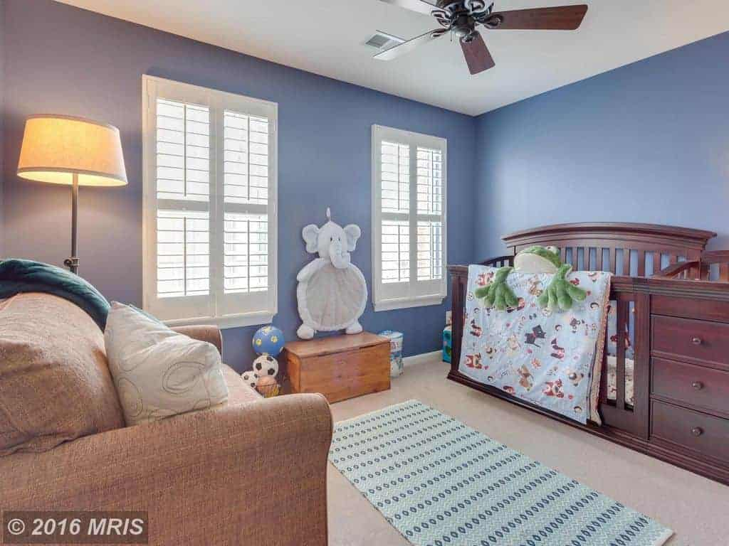 Blue nursery with a comfy armchair and wooden crib fitted with built-in drawers. It includes a ceiling fan and patterned runner that lays on the gray carpet flooring.
