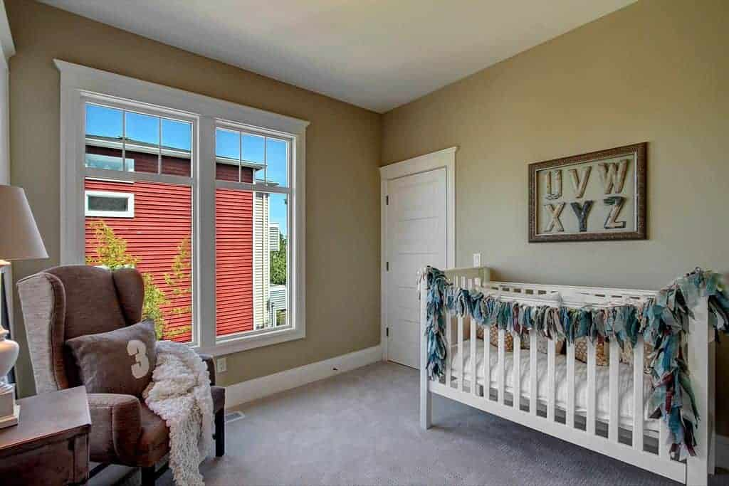 This nursery features a brown wingback armchair and white crib accented with an alphabet artwork. It has beige walls and framed windows inviting natural light in.
