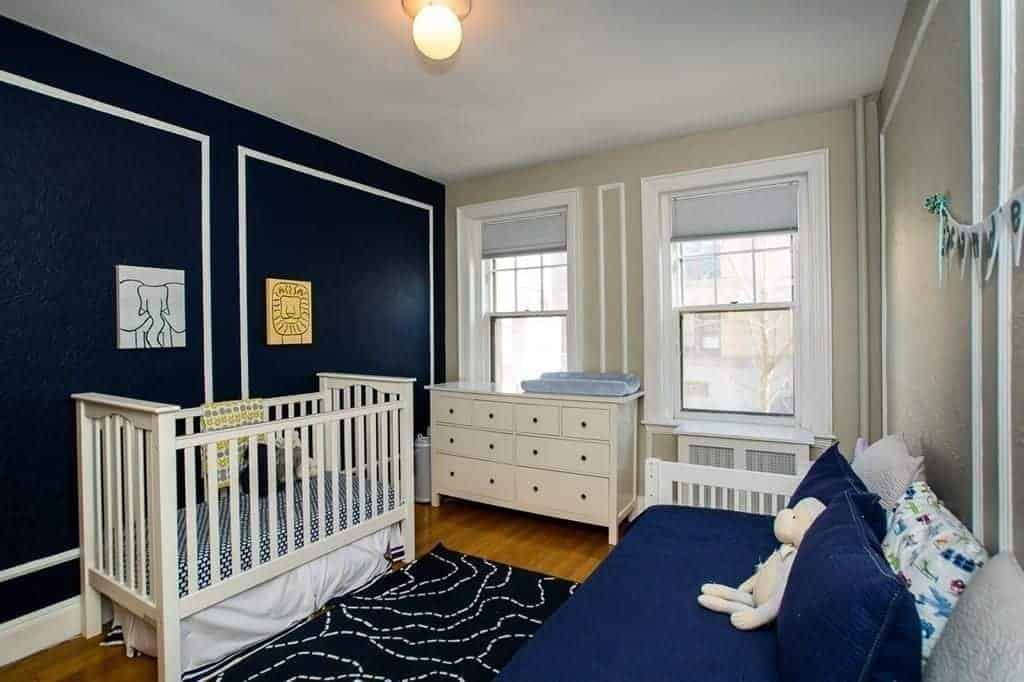 A skirted crib matches the white seat topped with navy blue cushion and fluffy pillows. It includes a drawer chest and black printed rug that lays on the rich hardwood flooring.