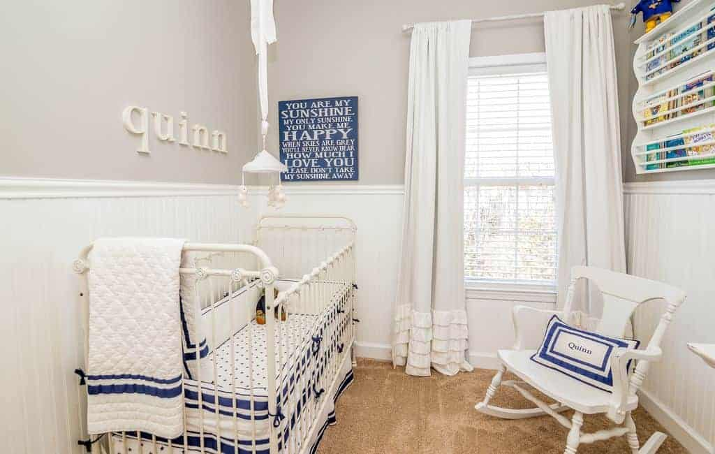 Light and airy nursery with a metal skirted crib that complements the white rocking chair and floating shelf mounted above the beadboard wall.