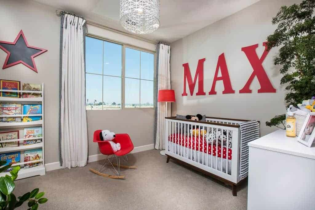 This nursery offers a modern red chair and sleek white crib accented with large, red letters spelling out baby's name. It is illuminated by a stylish drum pendant light and red floor lamp by the glazed windows.
