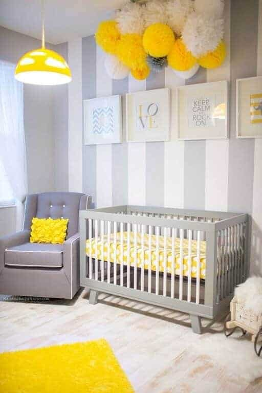 A yellow dome pendant light illuminates the gray armchair in this cheerful nursery decorated with pompoms and white framed artworks mounted on the striped accent wall.