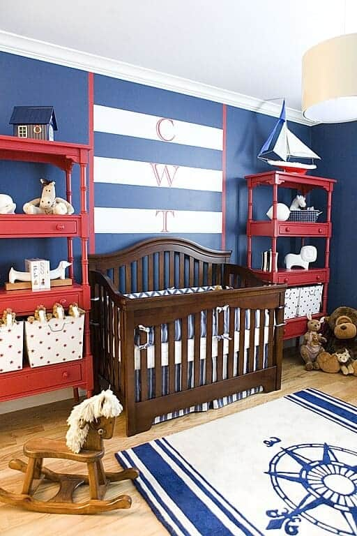Nautical themed nursery with a wooden rocking horse, navy compass rug and a dark wood crib flanked by red shelving units that are filled with toys and storage boxes.