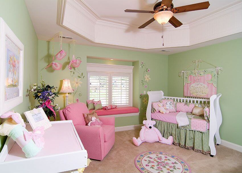 Garden themed nursery showcases a skirted crib accented with a cute tapestry along with a window seat nook that's lined with a pink cushion matching the armchair.