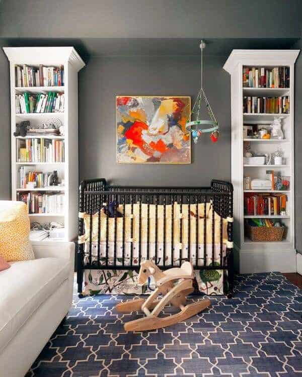 Colorful artwork hangs above the black crib flanked by white shelving units against the gray inset wall. It is accompanied by a cozy sofa and wooden rocking horse over the deep blue patterned rug.