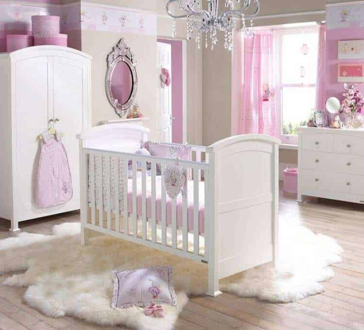 Glamorous nursery decorated with a crystal chandelier and gorgeous mirror mounted next to the arched wardrobe. There's a white crib in the middle that sits on a white faux fur rug over wide plank flooring.