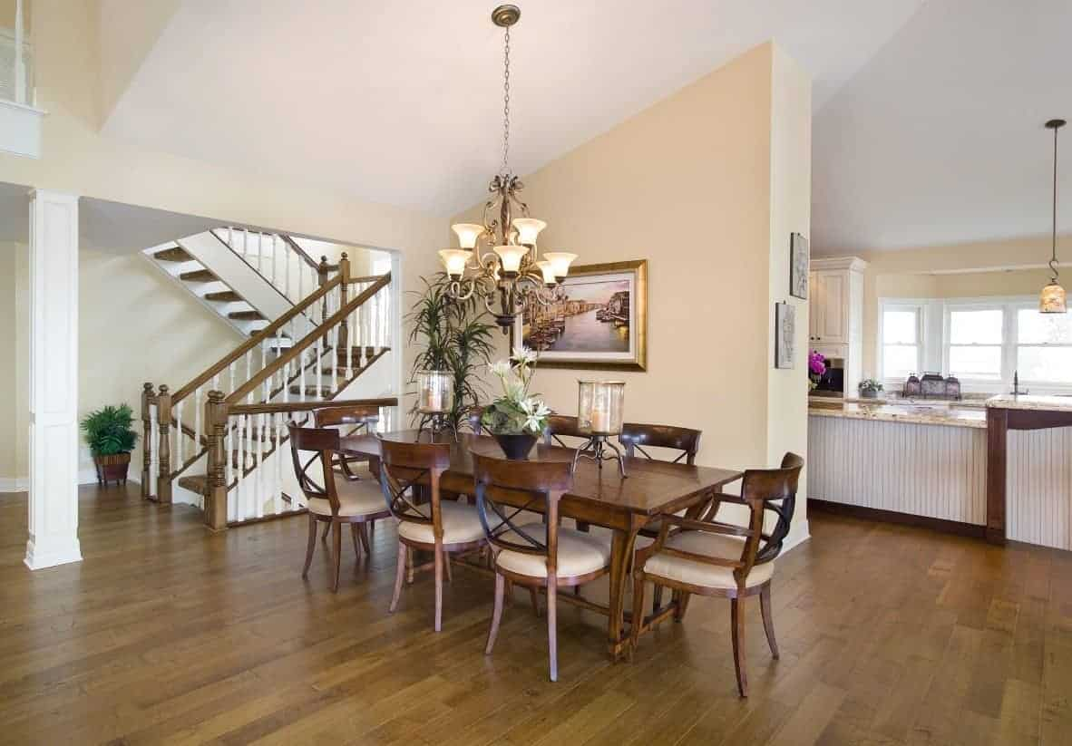 This is an elegant Beach-style dining room with dark hardwood flooring that matches with the wooden dining table that is surrounded by matching wooden chairs with beige cushioned seats matching the walls and the elegant chandelier.