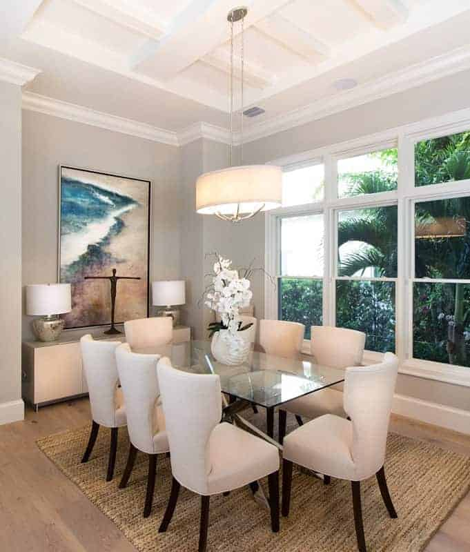 The hardwood flooring of this Beach-style dining room is topped with a woven area rug that complements the dark wooden legs of the wing back chairs surrounding the glass-top dining table topped with an oval beige pendant light.
