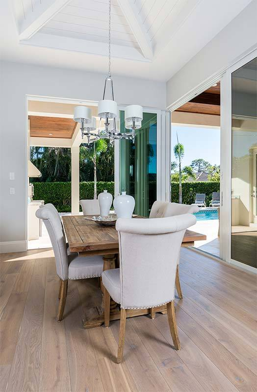 The farmhouse-style wooden dining table is perfectly paired with the legs of the light gray cushioned chairs that match the walls. These walls are dominated by large sliding glass doors augmenting the modern chandelier.