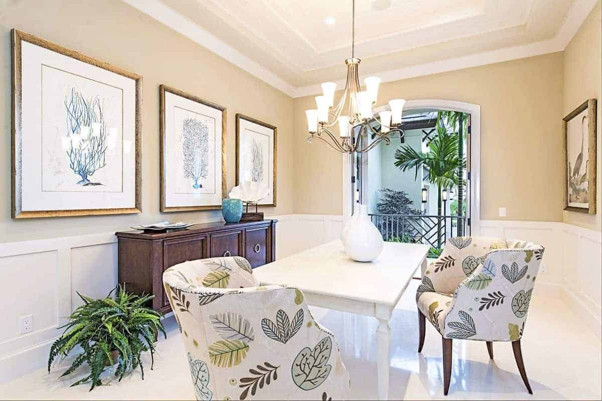 The elegance of this Beach-style dining room stems from the intricate chandelier hanging over the white wooden table. It casts warm yellow light that augments the beige walls adorned with framed artworks of leaves and trees matching the patterns on the cushioned chairs.