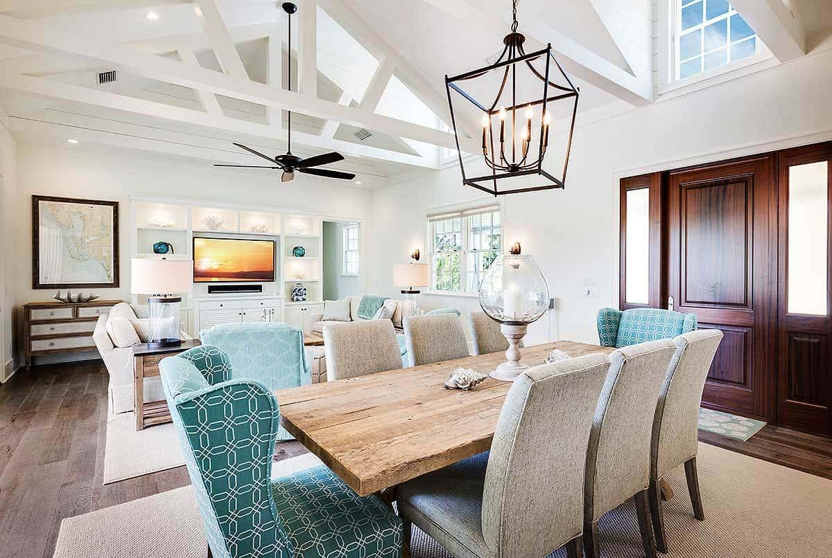 The two heads of the table have matching green patterned chairs on them that stands out against the rest of the chairs that have a light gray hue complementing the wooden table topped with a farmhouse-style pendant light.