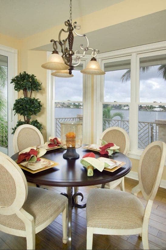 This is an intimate dining room with a circular table that sits four persons on beige oval-backed chairs and given a breathtaking view of the watery scenery outside of the large glass windows surrounding the dining area.