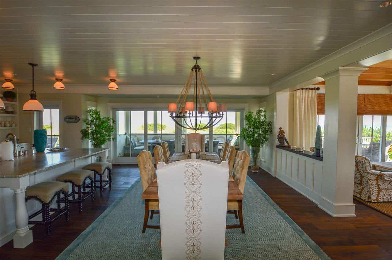 The large structure of the farmhouse-style chandelier as well as its reddish glow catches the attention in this Beach-style dining room with a blue woven area rug covering the dark hardwood flooring contrasted by the white shiplap ceiling.