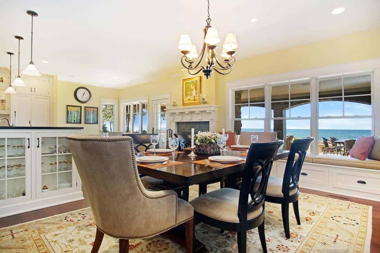 This Beach-style formal dining room has an elegant dark wooden dining table that matches the elegance of the wrought-iron chandelier and the black wooden dining chairs that stand out against the yellow patterned area rug over the hardwood flooring.