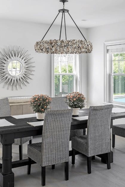 The perfect combination of black and gray elements makes this formal dining room an exceptional design with its large black wooden table that goes perfectly with the gray woven dining chairs with black legs that stand out against the gray hardwood flooring.