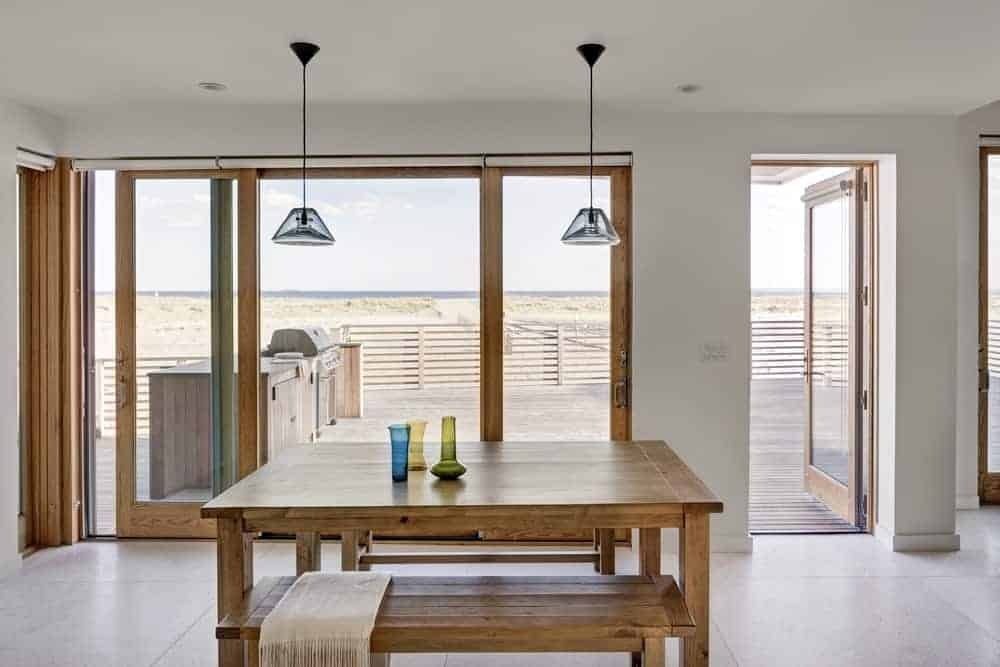 This is a simple and informal dining area with a simple wooden table paired with a couple of wooden benches. This is a match for the frames of the large sliding glass doors that opens to an amazing ocean view that elevates the simple dining experience.