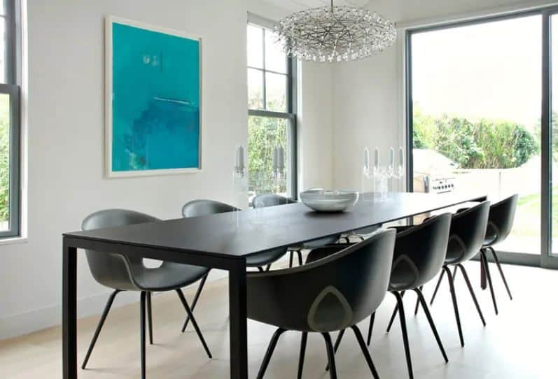 The modern black dining table is paired with equally modern and black dining chairs. These stand out against the light hardwood flooring and the white walls adorned with a colorful artwork as well as the peculiar crystal lighting.