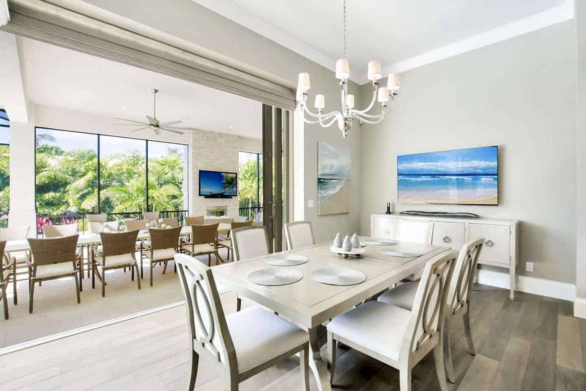 This simple dining room has light gray walls that are perfectly matched with the dining table and its cushioned chairs that complement the hardwood flooring. The light gray walls are adorned with colorful artwork and a mounted TV.