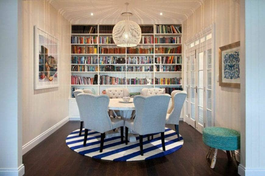The main feature of this dining room is the entire wall dominated with bookshelves filled with books providing a warm and cozy background for the simple round dining table able to accommodate six cushioned chairs over a white and blue striped area rug.