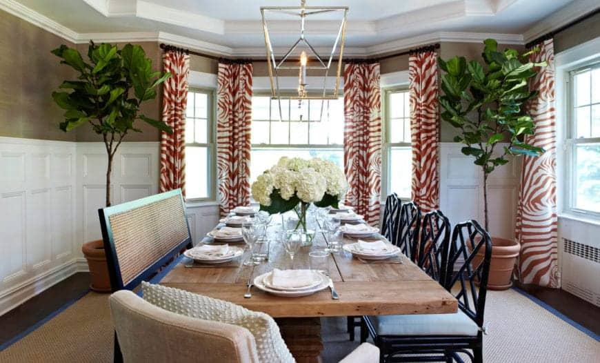 This formal Beach-style dining room is illuminated by the natural lights coming in from the windows that are flanked with patterned orange curtains and potted plants that set a colorful background for the wooden table paired with black chairs.