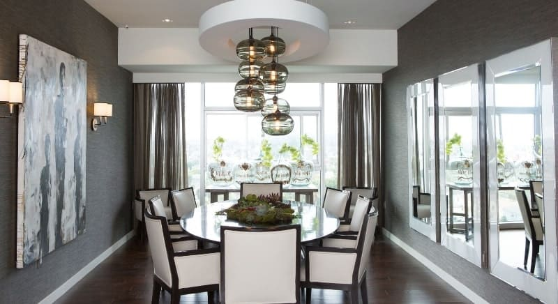 The round table is surrounded by dining chairs with white leather cushions that stand stand out against the dark hardwood flooring and dark gray wallpaper of the walls adorned with a painting and large glass windows.