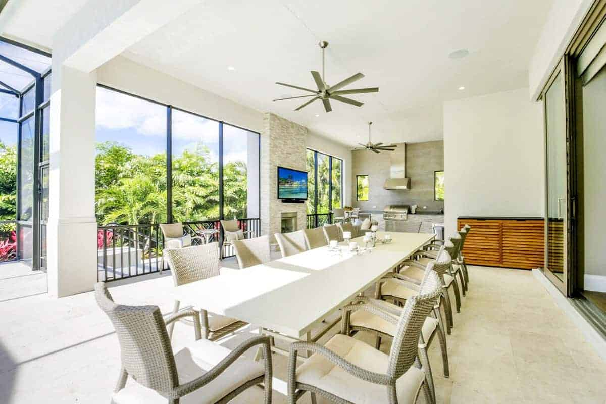 This is a large Beach-style dining area specifically designed to enjoy the surrounding lush greenery while dining on the long beige table surrounded by woven wicker chairs with beige cushioned seats matching the flooring that is complemented by the high white ceiling.