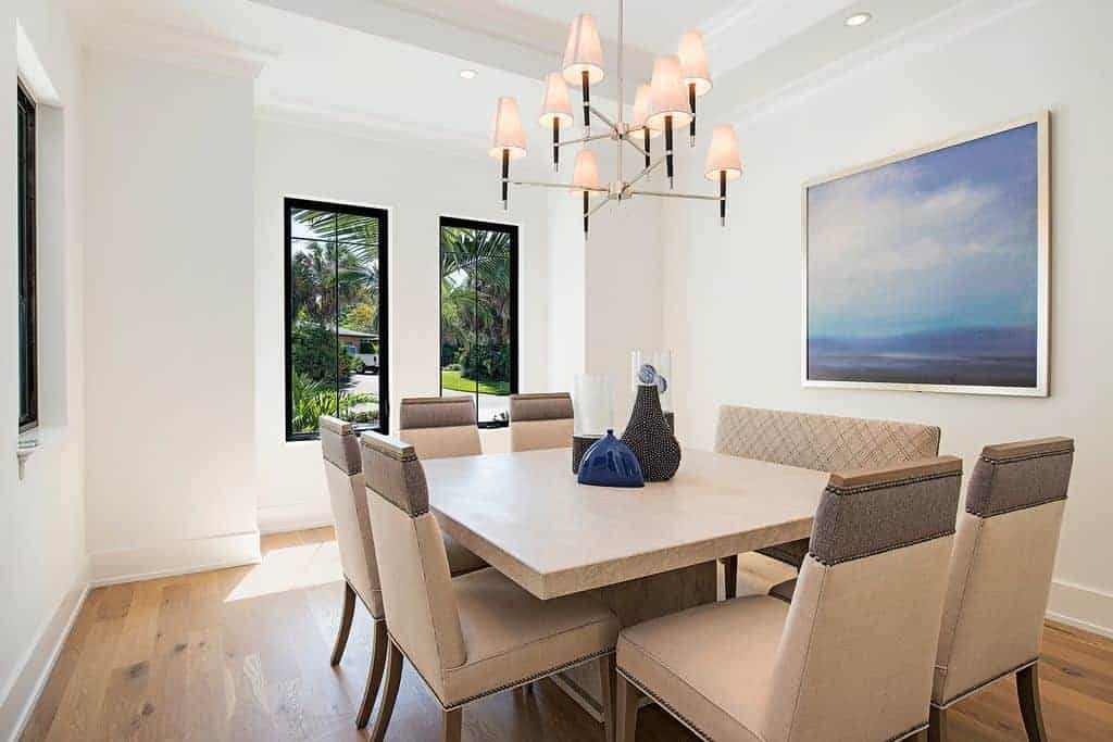 The modern chandelier complements the white tray ceiling blending in with the white walls decorated with a colorful painting looking over the beige wooden table surrounded similar-hued dining chairs.