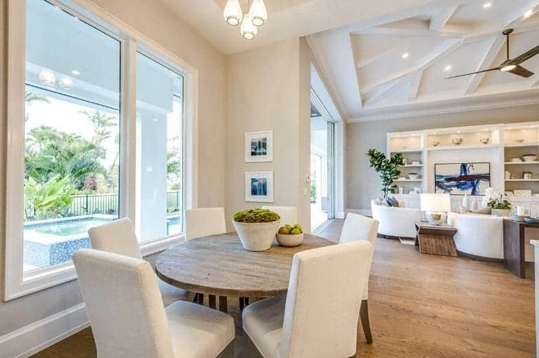 This simple and informal Beach-style dining area near the living room area has a rustic round wooden table paired with cushioned dining chairs matching the small pendant lights hanging from the high ceiling complemented by tall windows.