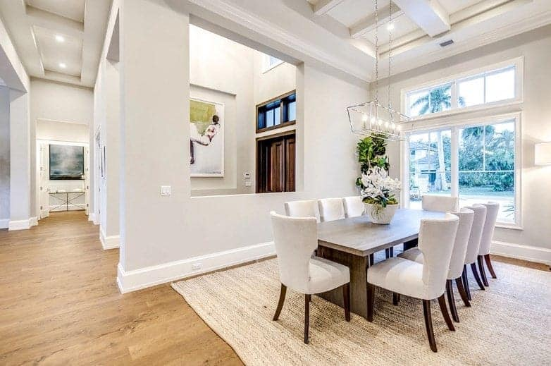 This formal dining room by the entrance of the house has a large woven area rug marking the area over the hardwood flooring matching the rectangular wooden dining table paired with wing back chairs that matches the white coffered ceiling.