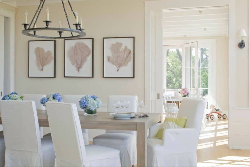 The dining chairs surrounding the wooden table have white slip covers that complement the light hardwood flooring and the beige walls adorned with framed leaf artworks that emphasizes the dark farmhouse-style chandelier.