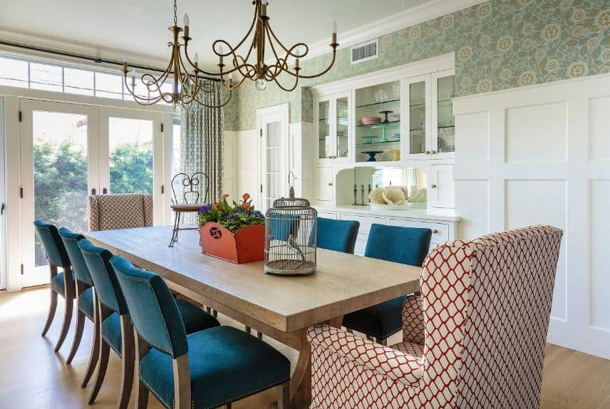 The long wooden dining table is topped with a couple of brass intricate chandeliers that matches the elegance of the green patterned wallpaper adorning the upper walls complementing the white walls that make the blue chairs stand out.