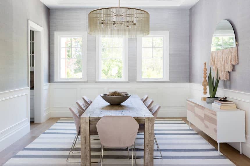 The hardwood flooring of this Beach-style dining room is topped with a striped gray area rug that contrasts the wooden table surrounded with modern chairs that match the light gray walls with white wooden wainscoting.