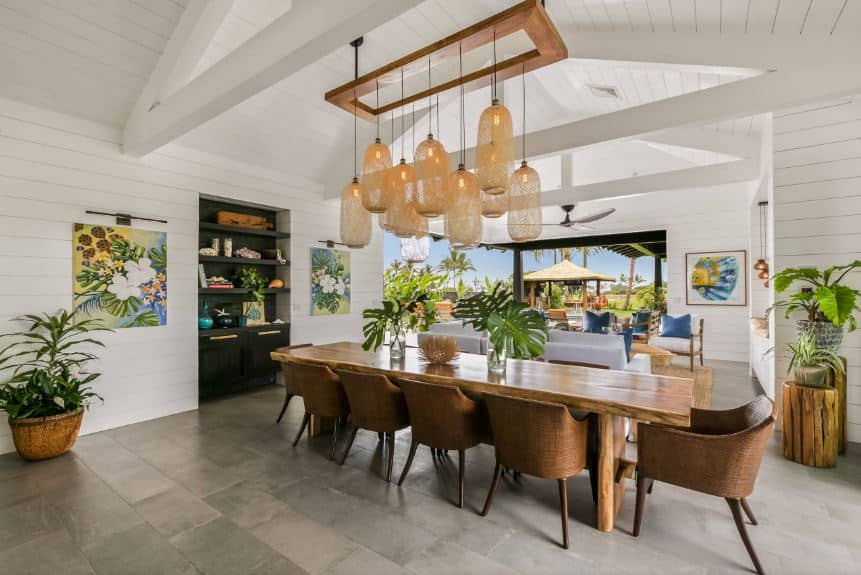 There are colorful floral paintings adorning the white shiplap walls for a dash of color that complements the wooden and rustic elements of the long table and its chairs topped with multiple pendant lights with woven basket covers.