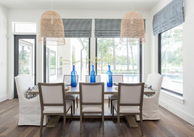 The two pendant lights over the wooden table has rustic woven basket hoods complementing the white ceiling that blends with the white walls dominated by windows casting natural lights on the white slipcovers of the two chairs at each head of the table.