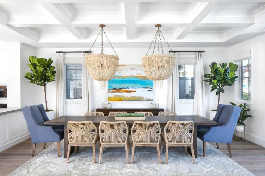 The white coffered ceiling supports the two pendant lights with rustic woven hoods that matches the woven rustic chairs of the long dark wooden dining table that contrasts the white walls adorned with a colorful painting and a couple of potted plants on the corners.