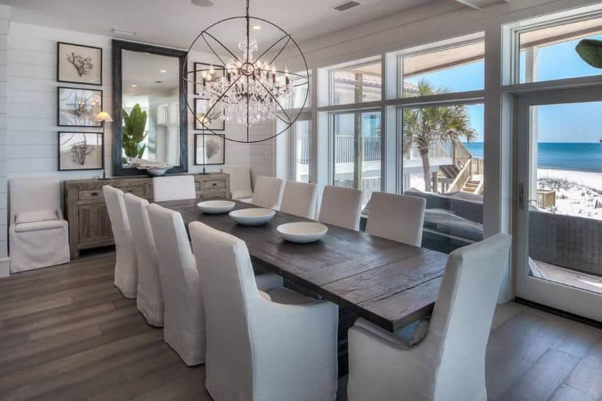 The long and narrow wooden table matches the hardwood flooring as well as the dining room cabinet by the white shiplap wall that is adorned with a large rectangular mirror flanked by framed artworks that match the large spherical design of the crystal chandelier.
