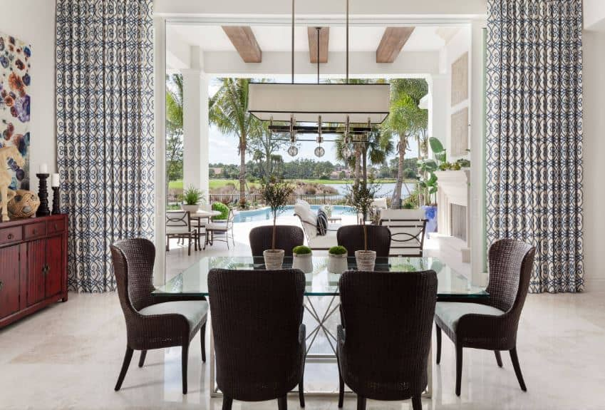 There is a modern rectangular row of lights hanging over the glass-top table that contrasts the dark woven dining chairs that stand out against the beige marble flooring illuminated by the opened large sliding glass doors flanked with patterned curtains.
