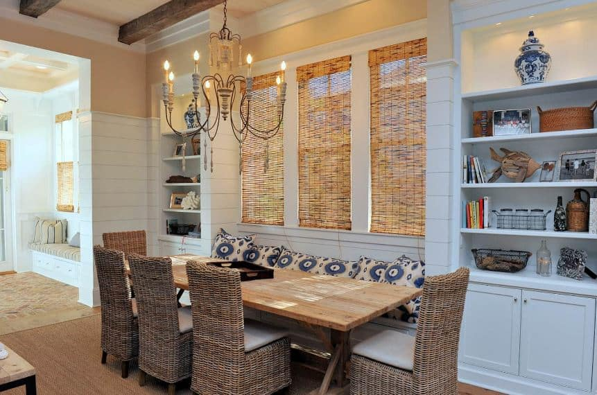 This is a charming and homey intimate dining room with a wooden table that matches well with the rustic woven rattan chairs that pairs well with the shades of the windows above the built-in bench with blue pillows that complement the blue shelves flanking the bench.