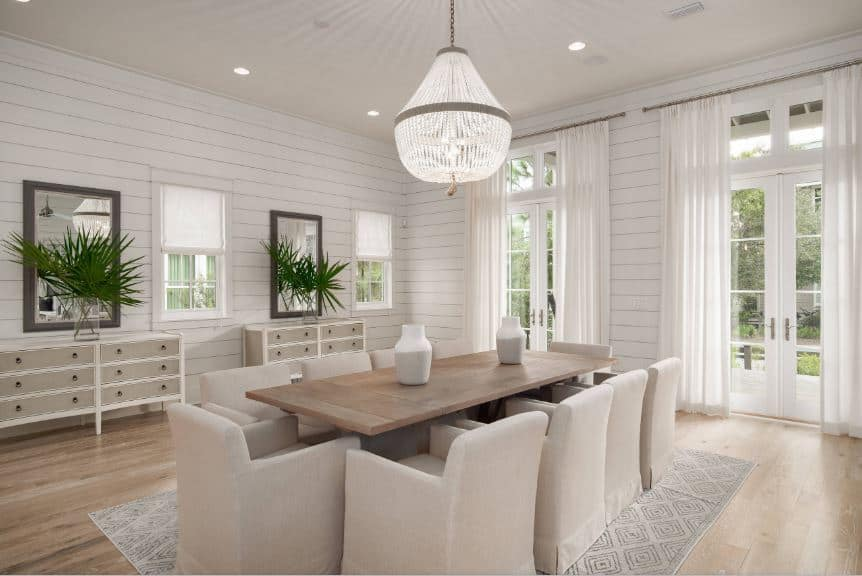 A brilliant and elegant crystal pendant light hangs from the white ceiling that goes well with the white shiplap walls adorned with a couple of dining room cabinets topped with mirrors. This sets a lovely tone for the wooden table surrounded with light gray chairs over a gray patterned area rug.