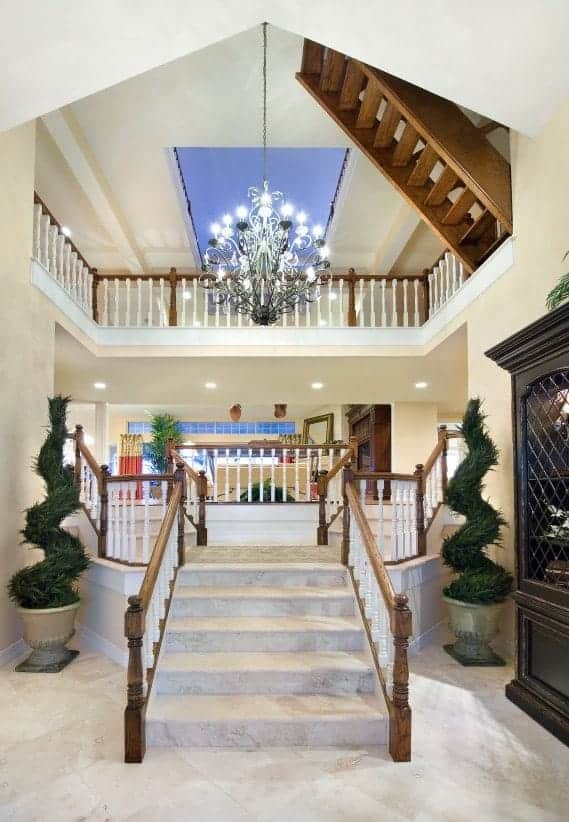 This small Beach-style foyer with white cathedral ceiling has a full view of the two levels of the house through a large hall that is dominated by a large elegant and intricate chandelier casting off white light that brightens the beige marble flooring.