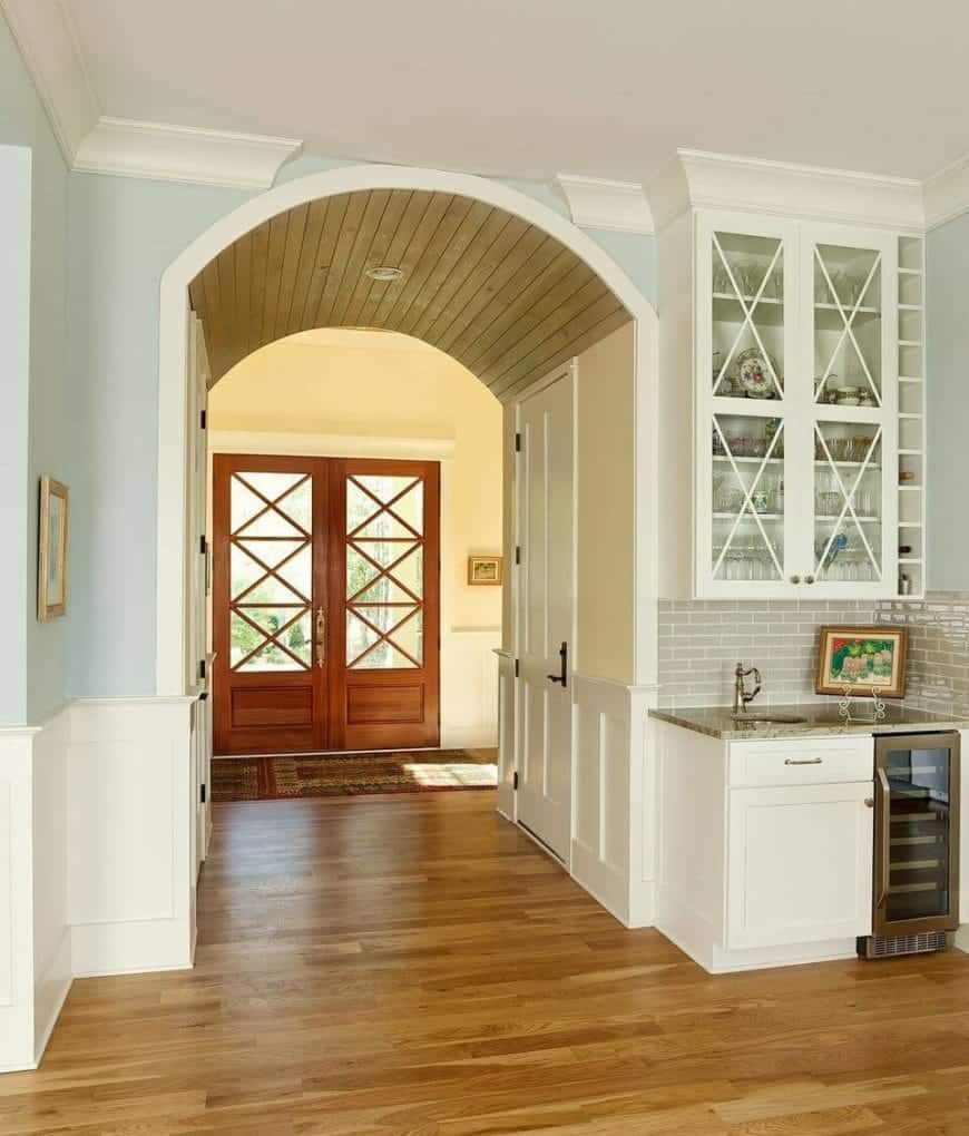 The charming double doors that have a wooden frame and glass panels works well with the hardwood flooring of the interiors and covered with a colorful area rug. This contrasts the white wainscoting of the beige walls leading to a beautiful arched entryway.