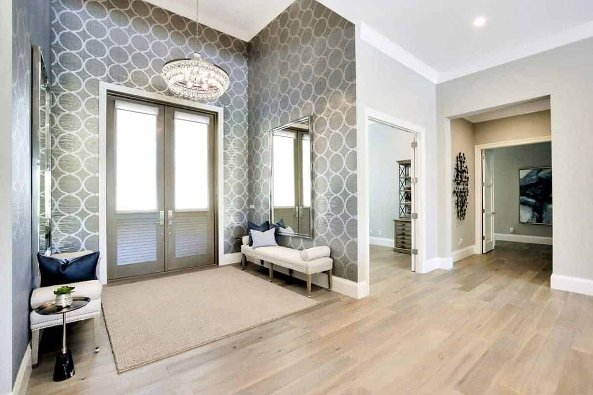 This bright and elegant Beach-style foyer has gray patterned wallpaper dominating the walls illuminated by a brilliant white crystal chandelier hanging over the woven area rug that covers the hardwood flooring matching the double doors that has glass panels on it.