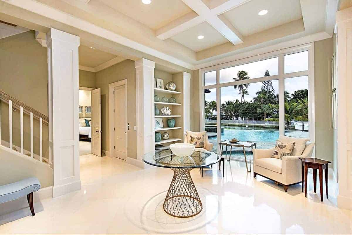 Upon entry of this Beach-style foyer, you are welcomed by a circular glass-top table with a brass geometric body bearing a white bowl. This is in the center of the beige flooring underneath the high beige coffered ceiling filled with recessed lights.