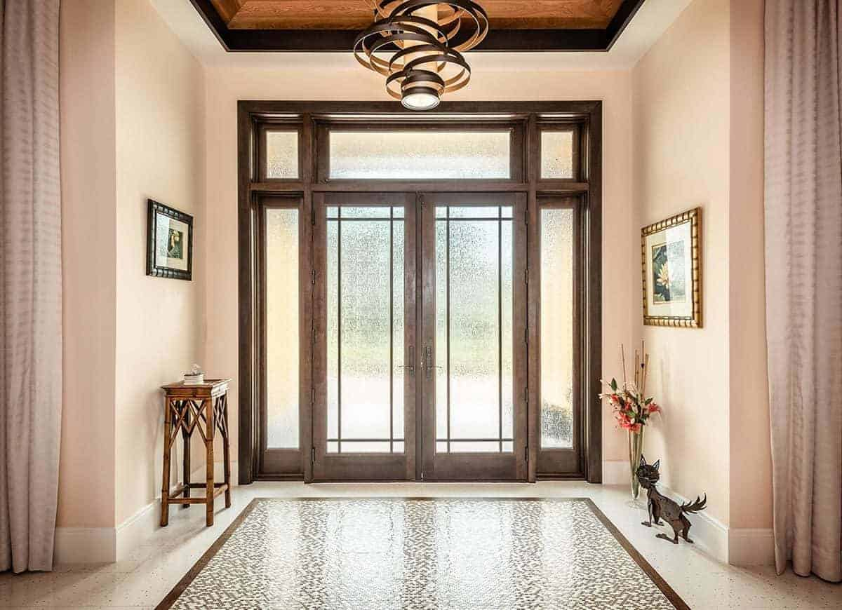 This eclectic Beach-style foyer is adorned with a cat decoration along with framed artworks mounted on the beige walls. This is given a nice background of the brilliant main double doors dominated by frosted glass that brings in an abundance of natural light.