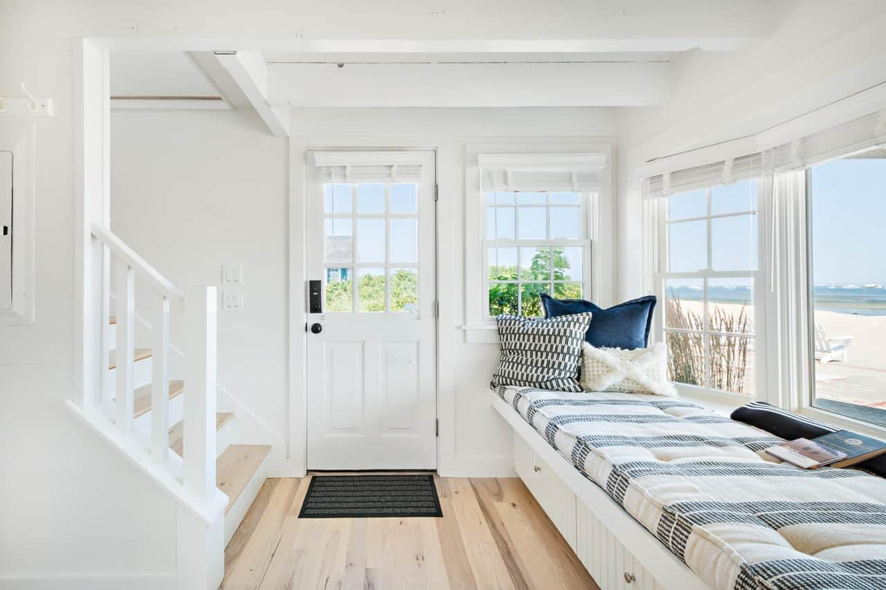 This is a brilliant Beach-style foyer dominated by a seaside view through the wide glass windows with a built-in cushioned bench right beside the white main door that matches the white ceiling with exposed beams.