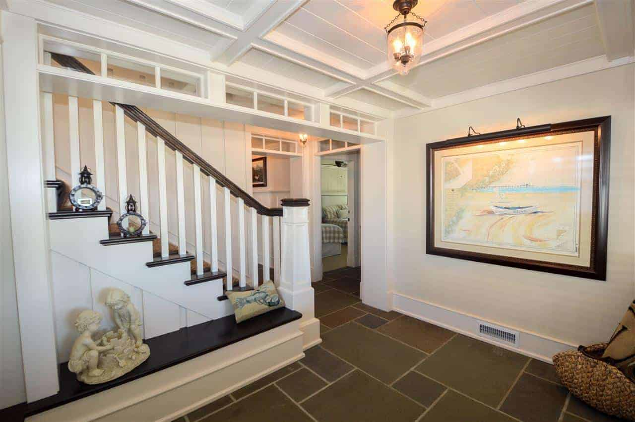 The earthy hues of the flooring in this foyer is contrasted by the stark white walls adorned with a large seaside painting and the white coffered ceiling adorned with a warm yellow pendant light illuminating the built-in bench on the side.