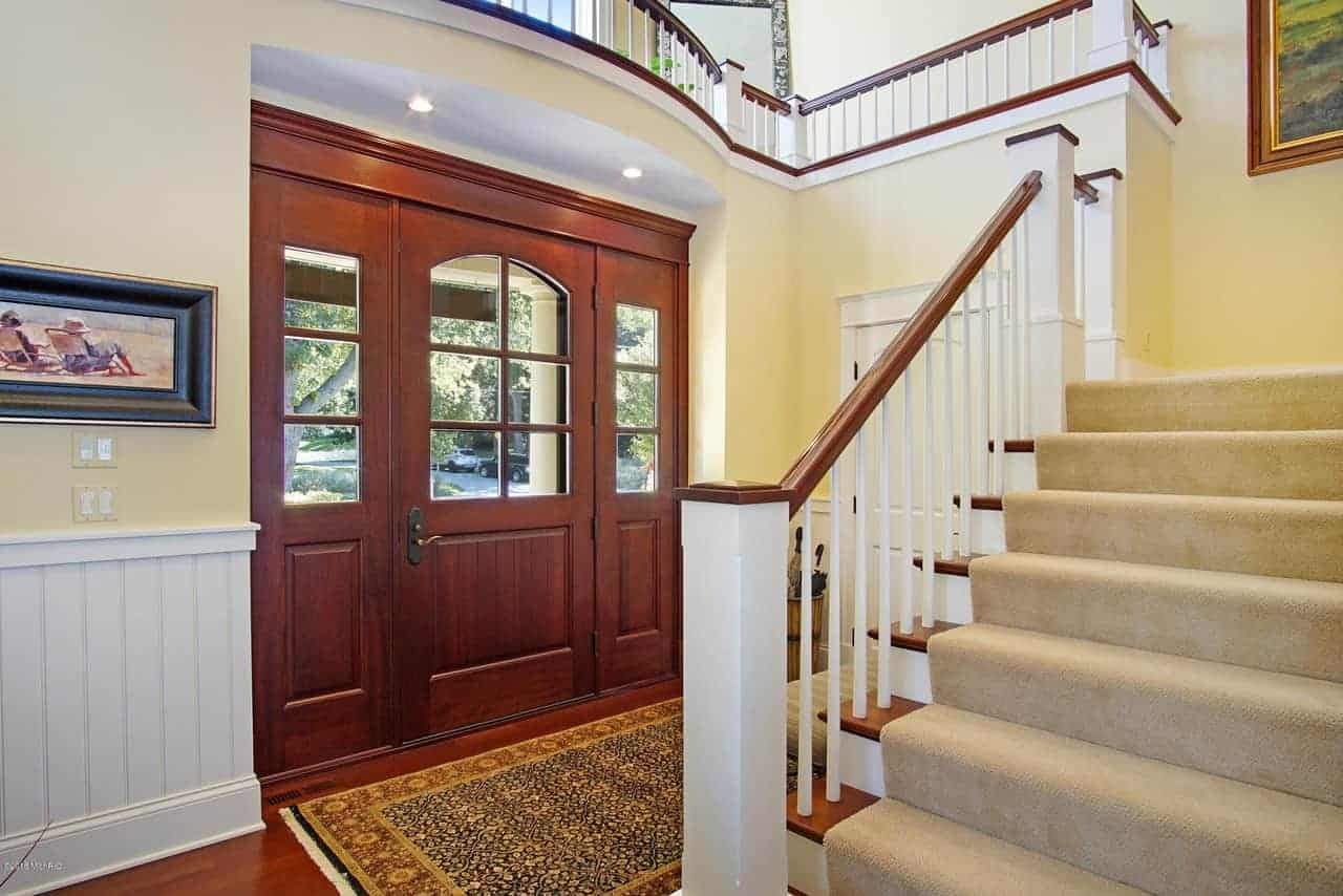 This Beach-style foyer has a bright and cheerful welcome to those who enter the wooden main door with glass panels. This matches the hardwood flooring that is covered with a patterned area rug complementing the beige walls and white wainscoting.